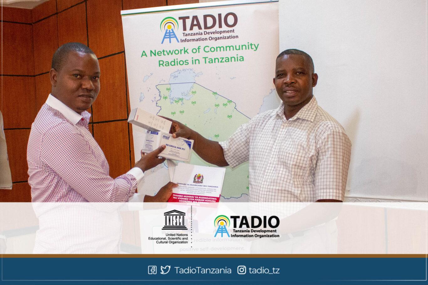 Meneja wa Redio Jamii FM, Bw. Amua Rushita akikabidhiwa vifaa vya kujikikinga na magonjwa ya mlipuko na Mwenyekiti wa TADIO, Bw. Prosper Kwigize
