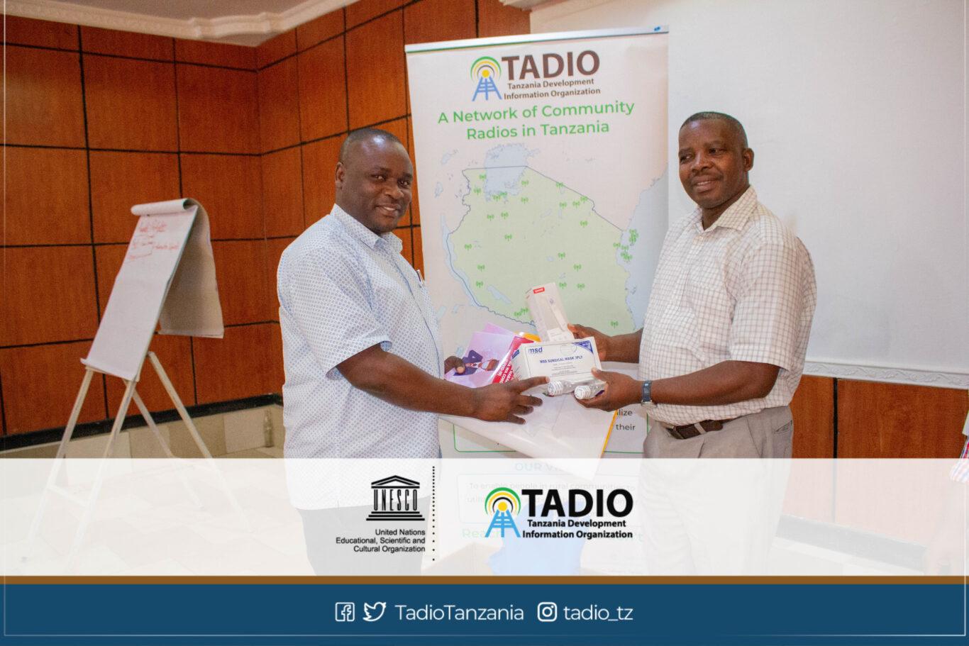 Meneja wa Chai FM, Bw. Ally Malwenga akikabidhiwa vifaa vya kujikikinga na magonjwa ya mlipuko na Mwenyekiti wa TADIO, Bw. Prosper Kwigize