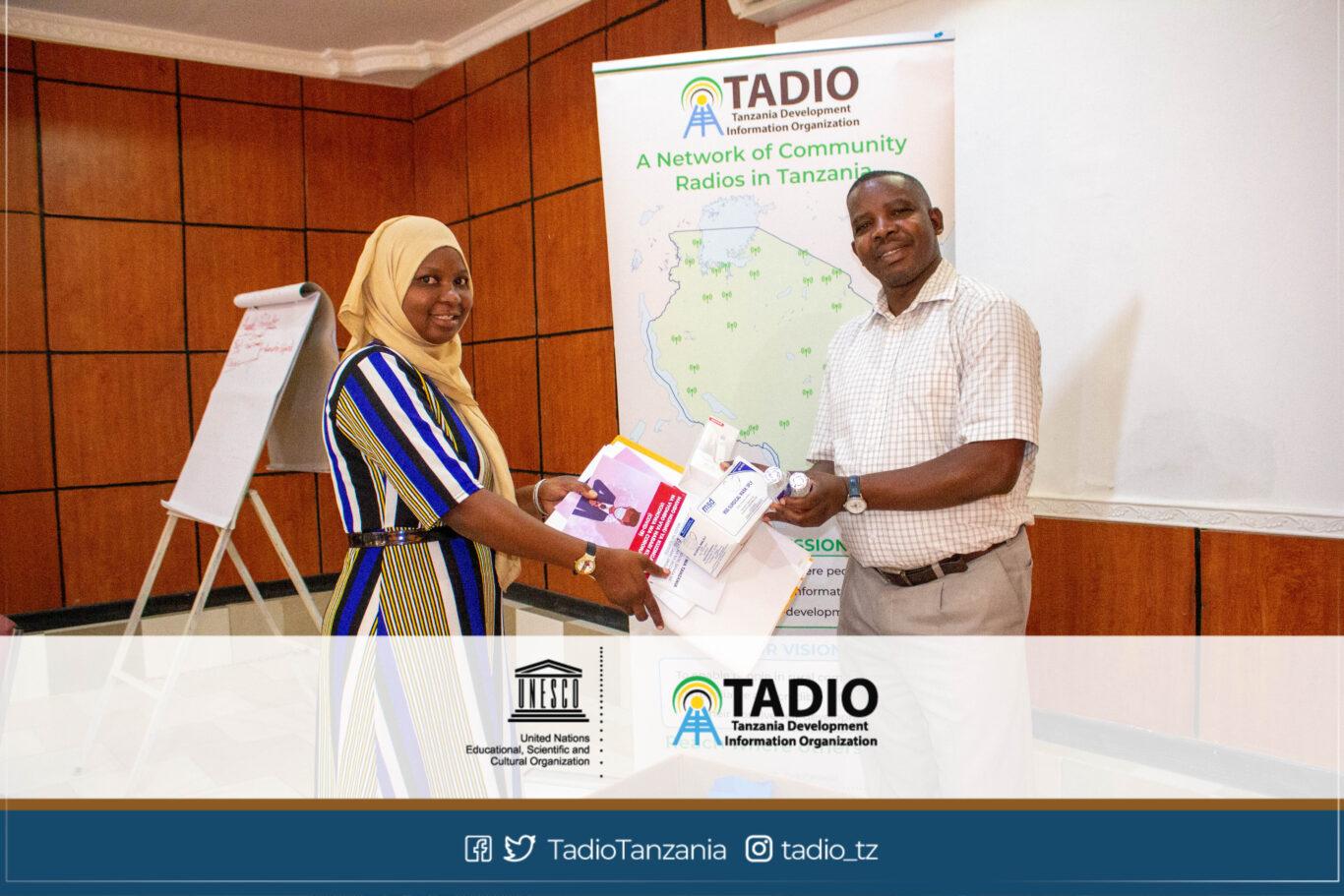 Kaimu Meneja wa Uyui FM, Bi. Nyamiz Mdaki akikabidhiwa vifaa vya kujikikinga na magonjwa ya mlipuko na Mwenyekiti wa TADIO, Bw. Prosper Kwigize