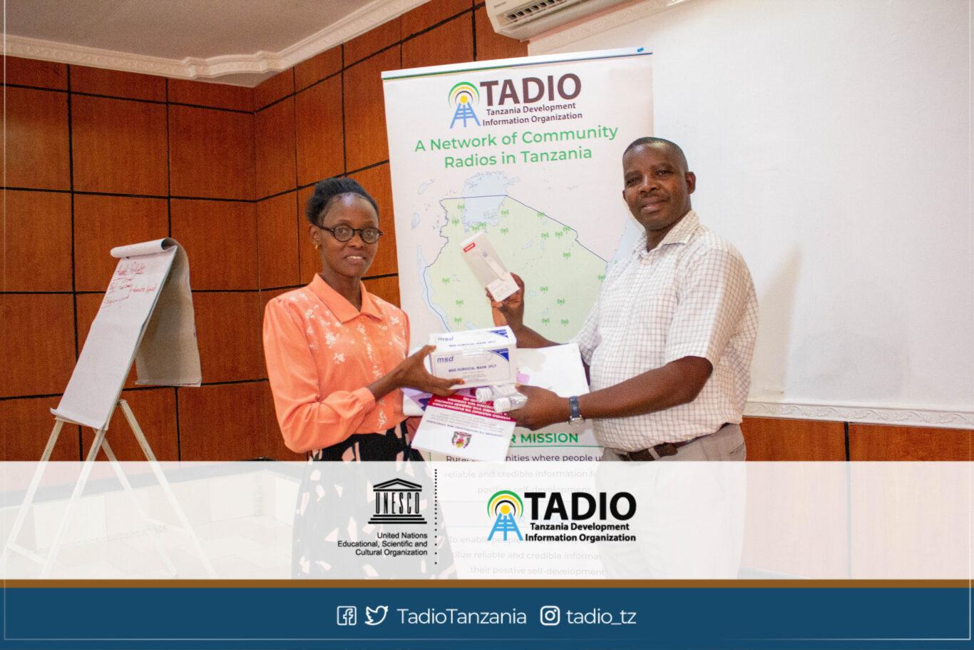 Meneja wa Dodoma FM, Bi. Zania Miraji akikabidhiwa vifaa vya kujikikinga na magonjwa ya mlipuko na Mwenyekiti wa TADIO, Bw. Prosper Kwigize