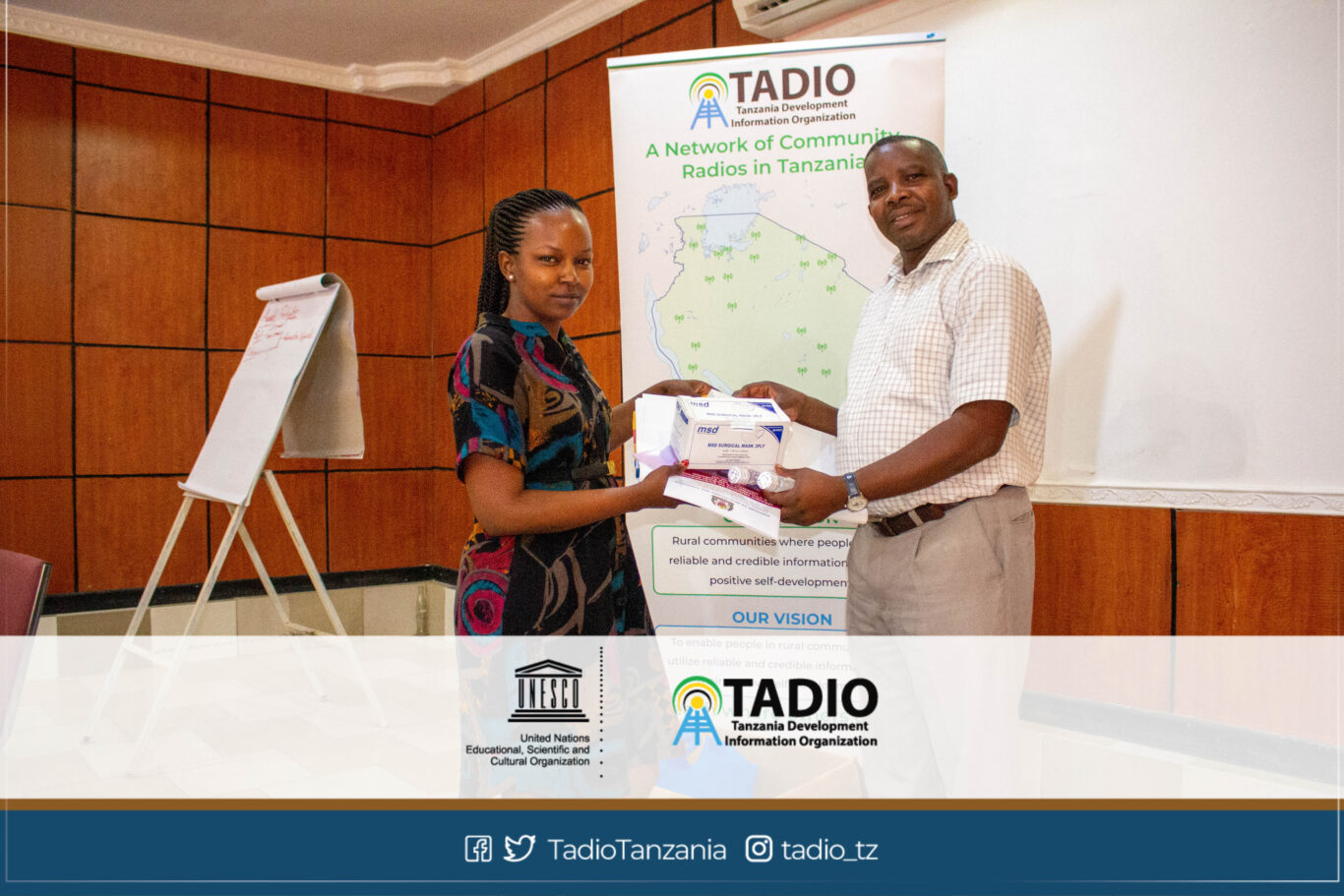 Huheso FM Manager, Ms. Chevawe Mandari receiving health protection equipment from TADIO Chairperson, Mr. Prosper Kwigize