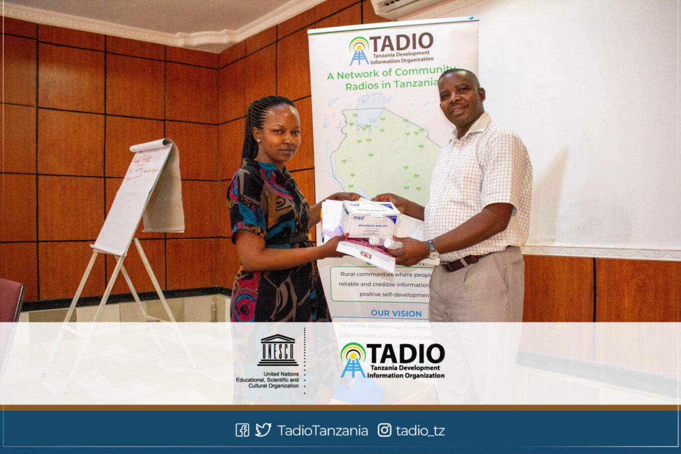 Meneja wa Huheso FM, Bi. Chevawe Mandari akikabidhiwa vifaa vya kujikikinga na magonjwa ya mlipuko na Mwenyekiti wa TADIO, Bw. Prosper Kwigize