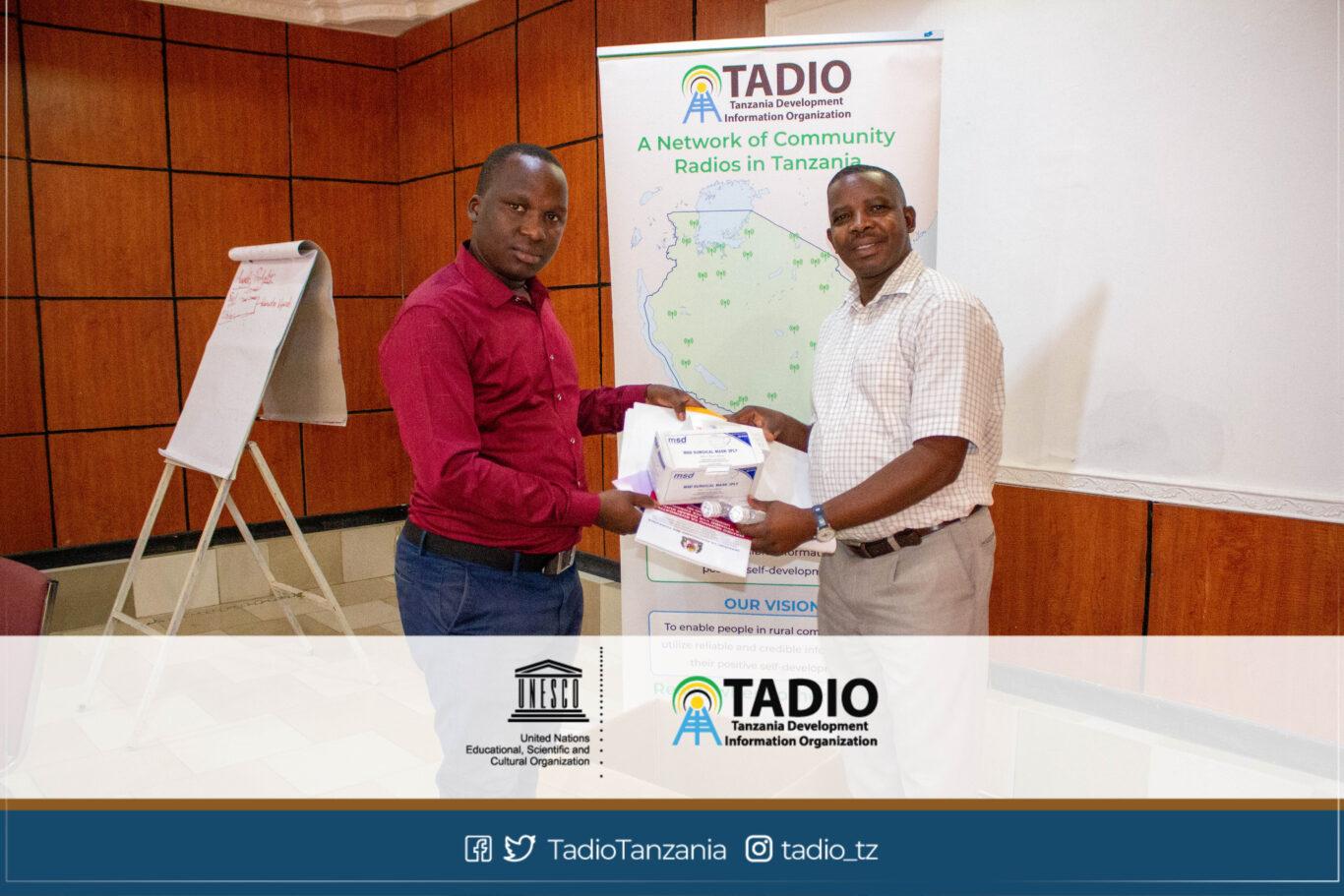 Meneja wa Sibuka FM, Bw. Daniel Manyanga akikabidhiwa vifaa vya kujikikinga na magonjwa ya mlipuko na Mwenyekiti wa TADIO, Bw. Prosper Kwigize