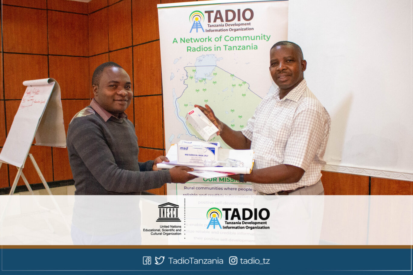 Mpanda FM Manager, Mr. Alinanuswe Edward receiving health protection equipment from TADIO Chairperson, Mr. Prosper Kwigize