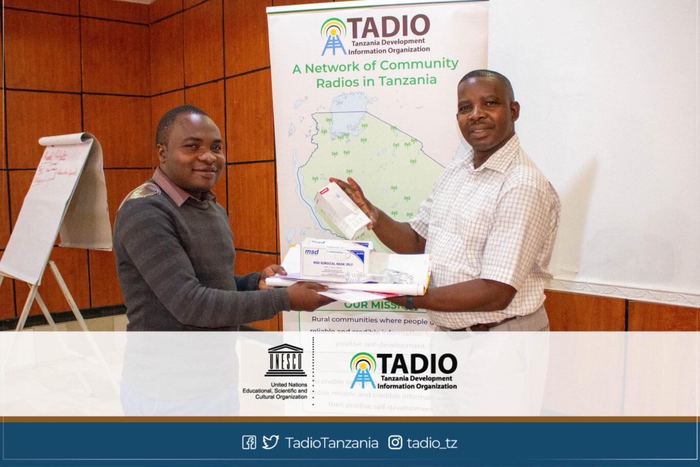 Meneja wa Mpanda Radio FM, Bw. Alinanuswe Edward akikabidhiwa vifaa vya kujikikinga na magonjwa ya mlipuko na Mwenyekiti wa TADIO, Bw. Prosper Kwigize