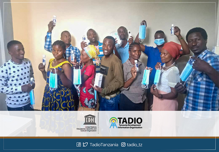 Journalists at Mazingira FM cheering after receiving the health protection equipment from TADIO and UNESCO